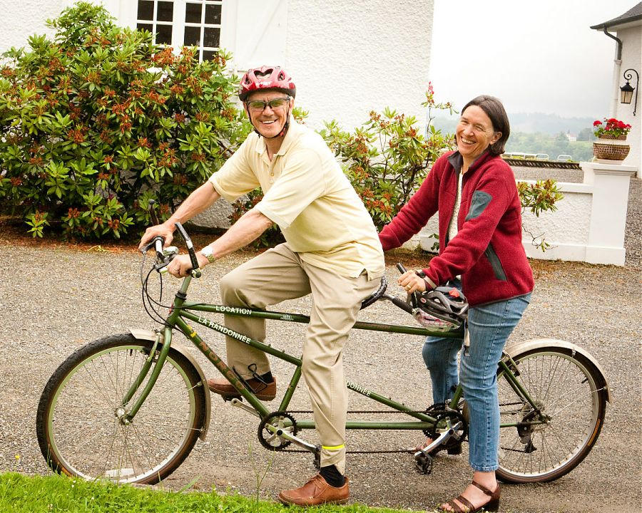man and woman on a tandem bicycle in the grounds of Clos Mirabel