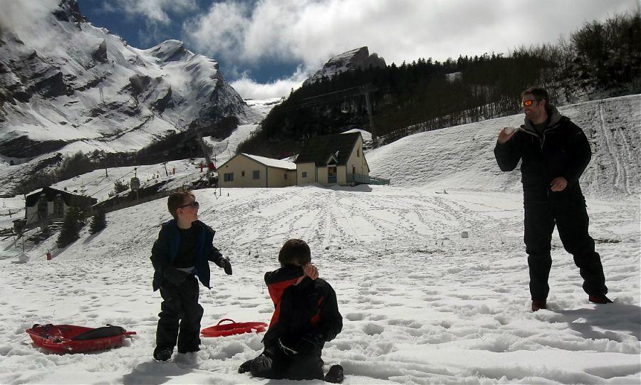 Enfant-jouant-dans-le-neige-en-face-des-montagnes