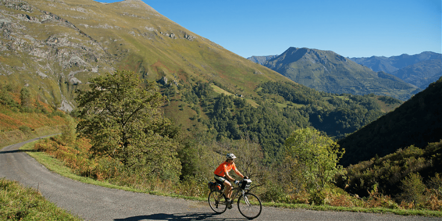 Man on bicycle with mountains in background and view of mountains