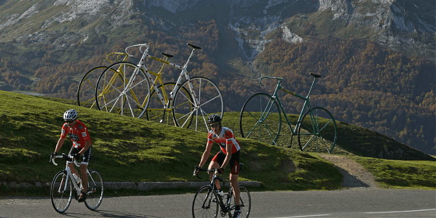 Men on bicycles with mountains and 3 bikes in background