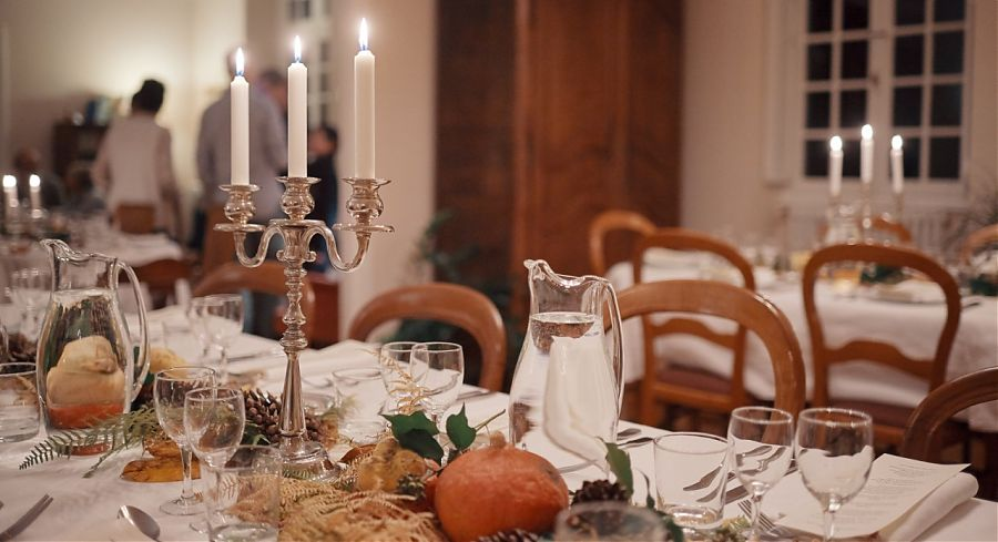 table with candles, glasses and knives and forks