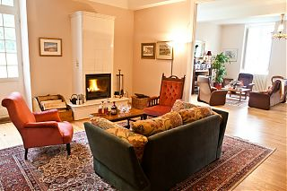 The double salon with sofas, armchairs and open fire