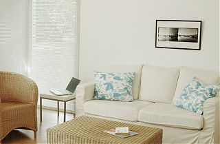 White sofa with blue cushions and armchair