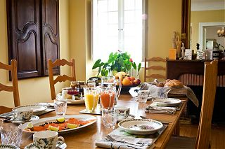 Table set for breakfast with fruit and bread and jams