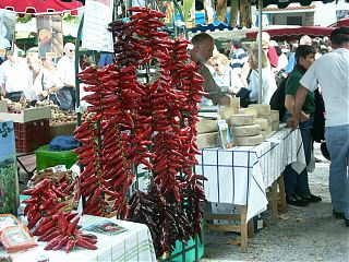 market scene with stalls selling peppers and cheese