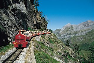 Red train with passangers in Pyrenees Mountains