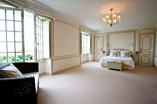 very large bedroom with cream carpet and white wall
