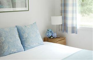 bedroom with blue cushions on bed and blue curtains