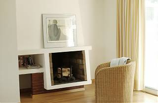 fireplace. wicker armchair, cream curtains and wooden floor