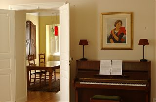 piano and dining room with paintings on wall