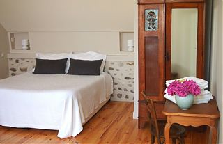 double bed in the winery studio with wardrobe and desk