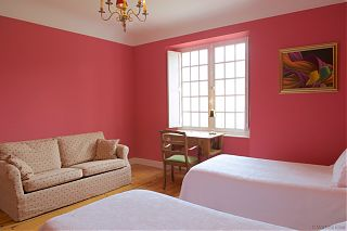 Pink guest bedroom with two single beds, sofa and desk