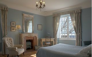 Blue guest room with double bed and view of Pyrenees