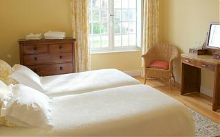 The yellow guest room with two single beds - garden views