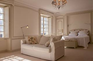 The Master bedroom with white sofa and kingsized bed