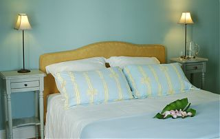 Double bed with blue wall and blue bed linen