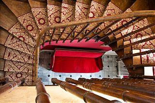 Sofa en rouge et escaliers dans le manoir de clos mirabel