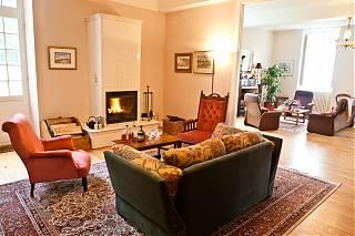 Salon double avec des sofas et poêle de céramique