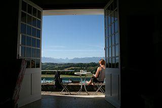 une femme assis au bord de la Piscine avec vue sur la vigne et les pyrénées.