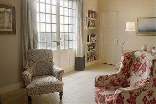 salon du chai - deux fauteuils et avec des étagères avec des livres