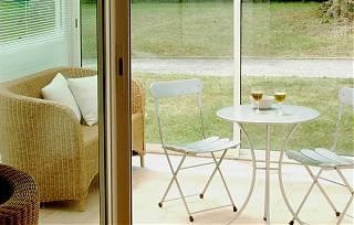 Véranda de la conciergerie - table, chaise, sofa et deux verres de vin