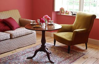 chambre rose avec sofa, table et fauteuil