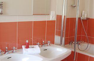 Salle de bain avec avec douche, lavabo, miroir et carreaux de couleur pêche