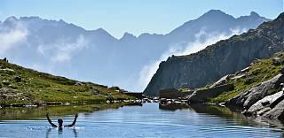 Randonnée - homme nage dans une lac dans les Pyrénées