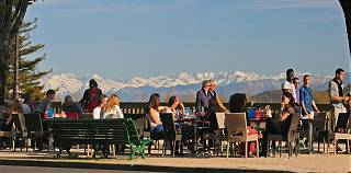 People-sitting-at-tables-outside-with-view-of-snow-capped-mountains-in-background