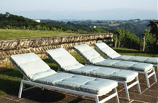 sun beds by the pool at Clos Mirabel with mountain views